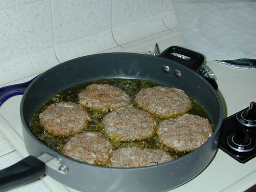 Crab cakes frying in a pan