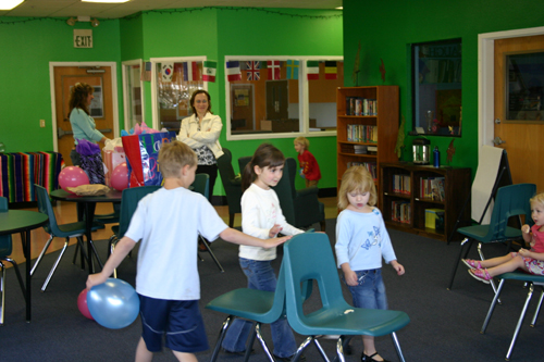 Children playing musical chairs, looking towards front right of room