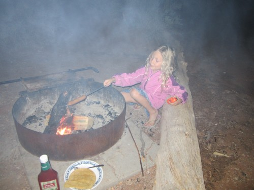 Miriam cooking hot dogs over the campfire