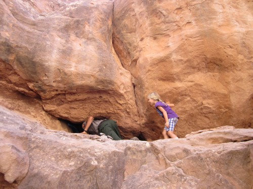 Miriam prepares to go through a tiny arch during the Fiery Furnace Tour at Arches National Park, Utah