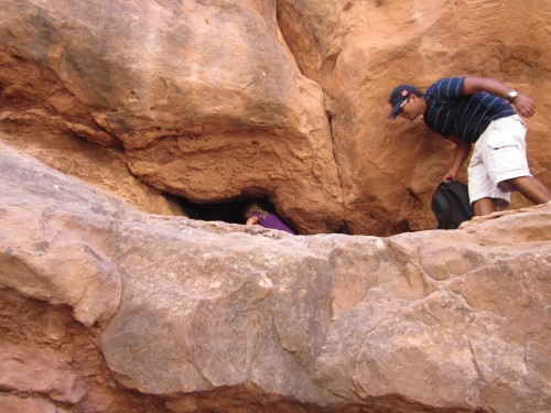 Miriam goes through a tiny arch during the Fiery Furnace Tour at Arches National Park, Utah